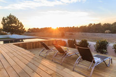 Chairs in modern house with wooden deck. Chairs in modern house with wood deck royalty free stock photography