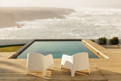 Chairs in modern house with wooden deck. And sea view Royalty Free Stock Images
