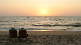 Chairs near coastline at sunset time. Two chairs near coastline at sunset time stock footage