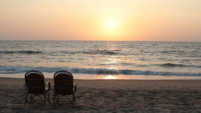 Chairs near coastline at sunset time stock footage