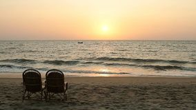 Chairs near coastline at sunset time. Two chairs near coastline at sunset time stock video