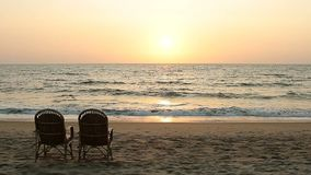 Chairs near coastline at sunset time. Two chairs near coastline at sunset time stock video footage