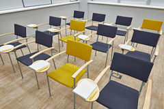 Chairs with notepads in empty classroom Royalty Free Stock Photo