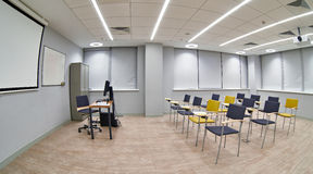 Chairs with notepads in an empty classroom Stock Photo