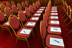 Chairs with notepads and pens in empty conference room Stock Photography
