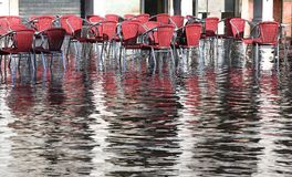 Chairs of the outdoor cafes with water at high tide Stock Images