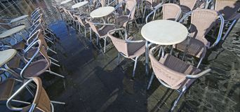 Chairs of the outdoor cafes with water at high tide Royalty Free Stock Photos