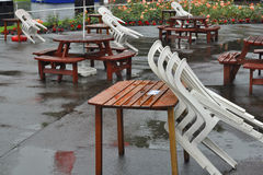 Chairs over tables in closed cafe. Rainy weather in Edinburgh: chairs in packs leaned over tables in outdoor cafe, taken in Princes Gardens Edinburgh Stock Image