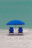 Chairs and parasol on beach. Blue beach chairs underneath parasol or umbrella on sandy beach with sea in background Stock Image