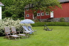 Chairs and parasol in a garden. Four chairs, a parasol and an anchor in a green garden Royalty Free Stock Photo