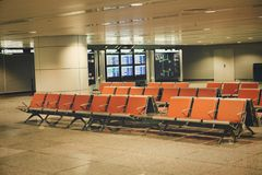 Chairs for passengers in the empty hall of Guangzhou Airport. The sign says `gate location» and the flight schedule China. stock images