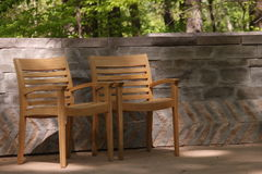 Chairs on a patio. Comfortable wooden chairs on a patio with a stone wall and forest in the background Stock Photography