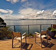 Chairs on Patio, Puget Sound, Washington. Bold, billowy clouds and blue sky reflect off of the calm waters in Puget Sound, Washington, near Seattle, making for a Royalty Free Stock Photography