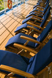 Chairs on Promenade Deck. Chaise lounge chairs lined up on the Promenade Deck of a luxury cruise ship Royalty Free Stock Images