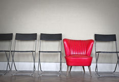 Chairs. Red chair standing out of some black chairs stock photos