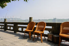 Chairs on riverside pavement with stone balustrade in sunny spri Royalty Free Stock Images