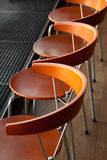 Chairs in a row. Modern wood and metal chairs lit by natural light Royalty Free Stock Photos