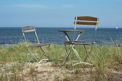 Chairs on sanddune at ocean Stock Photos