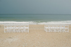 Chairs set up on the beach for a stormy wedding ceremony. Stock Image