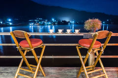Chairs sipping tea riverside at night time Royalty Free Stock Photo