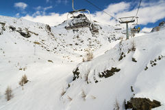 Chairs on ski lift above a rocky mountain in winter stock photo