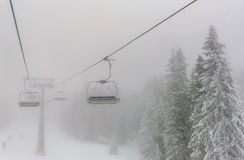 Chairs of a ski lift heading into the fog Royalty Free Stock Photography