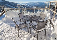Chairs on a snow covered deck with a chairlift tower in the background. royalty free stock image