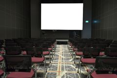 Chairs on stage of grand conference hall with white projector screen royalty free stock photos