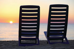 Chairs stand on beach near water stock image