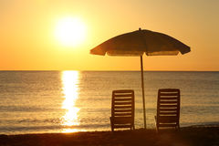 Chairs stand on beach under opened umbrella. Two empty chairs stand on  beach under  opened umbrella with  view on marine sunset Royalty Free Stock Photos
