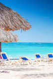 Chairs and straw umbrellas on stunning tropical beach Royalty Free Stock Images