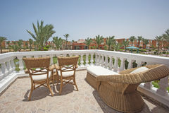 Chairs and sunbed on tropical hotel balcony Royalty Free Stock Images