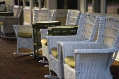 Chairs at Sunset. Whicker chairs sit on a porch at sunset Stock Image
