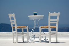 Chairs and table. White chairs and small table on a mediterrain balcony with nice view to the sea on a sunny day Royalty Free Stock Photography