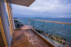 Condo balcony with Pattaya beach view. Chairs and table on balcony of luxury condo to see Pattaya beach view after sunset, Chonburi, Thailand Stock Photography