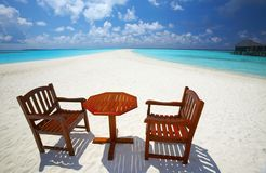 Chairs and table are on the beach. Two chairs and one table are on the coral sandy beach, Maldives royalty free stock photography