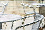 Empty Rainy Cafe Tables. Chairs and table belonging to a cafe remain deserted on a rainy winter day Royalty Free Stock Photography