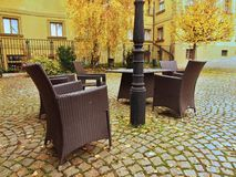 Chairs and table in garden at pedestrian precinct, yellow birch leaves on the granite pavement. Stock Images