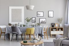Chairs at table with grey cloth in modern dining room. Interior with posters and lamp. Real photo stock photos