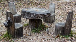 Chairs and table in park made of stub. Picnic area with chairs and table in park made of wood stub with foliage excellent place to rest Stock Photography