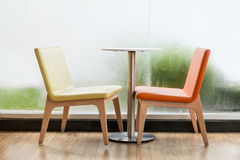 Chairs and table in the room. Colour chairs and table in the room with glass wall Royalty Free Stock Photography