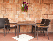 Chairs and table at the wall. Chairs and table standing at the brick wall Stock Photo