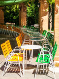 Chairs and tables at a bar terrace. Colorful chairs and round tables at a bar terrace stock images