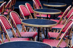 Parisian Cafe. A closeup of red chairs and empty round  tables in a parisian cafe Royalty Free Stock Photography