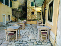 Patio dining, Corfu, Greece. Tables and chairs of outdoor restaurant on streets of Corfu, Greece Royalty Free Stock Photography