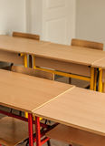 Chairs and tables inside empty classroom in primary school. Close up Stock Photography