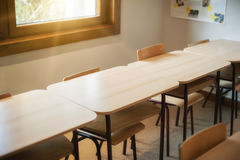 Chairs and tables inside empty classroom in primary school. Close up Royalty Free Stock Photo