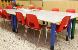 Chairs and tables of a kindergarten class without children. Red chairs and low tables of a kindergarten class without children royalty free stock photo