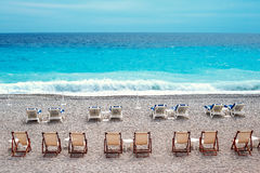 Chairs and tables on Nice beach along Promenade des Anglais Royalty Free Stock Photography