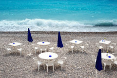 Chairs and tables on Nice beach along Promenade des Anglais Stock Image